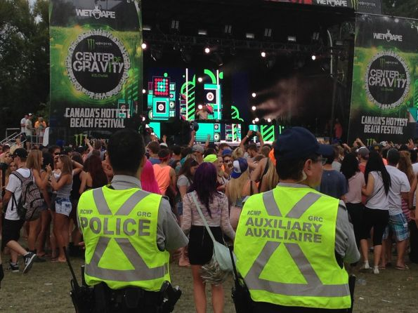 The boys in blue — or in this case neon green — look on during Wolfgang Gartner's set on Sunday. There was significant police presence throughout the concert grounds, ensuring everybody stayed safe in the fun environment. The next photo captures a female fan on the shoulders of a male friend in front of a giant screen as Wolfgang Gartner performs.